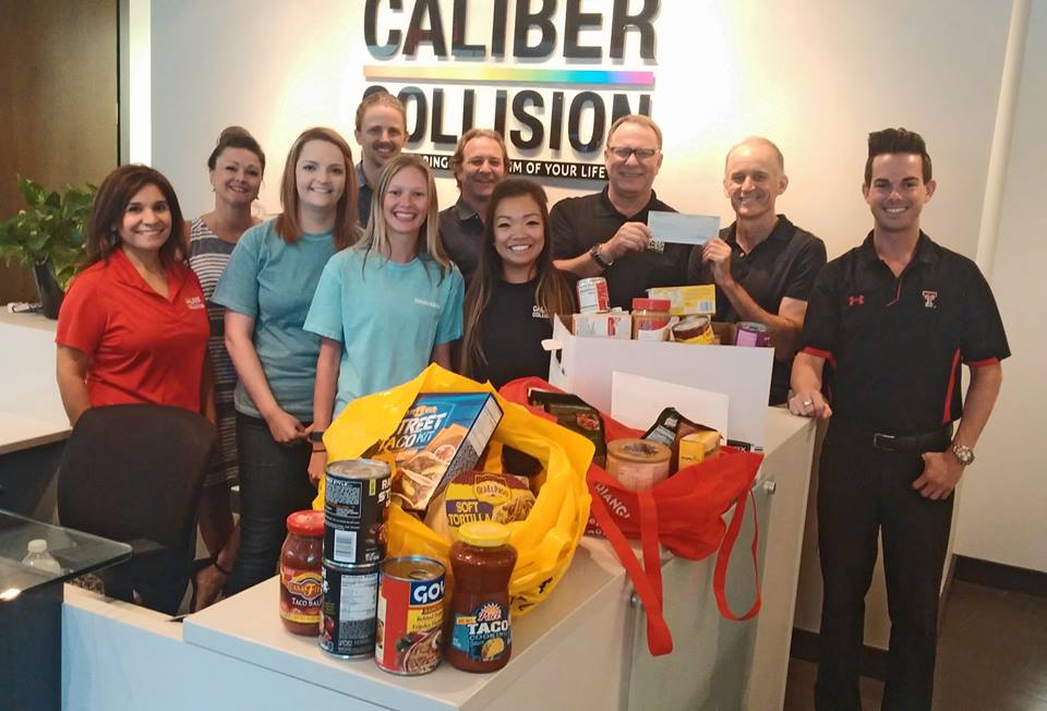 Caliber Collision and Johnson and Sekin staff pose with food drive items and a donation check.